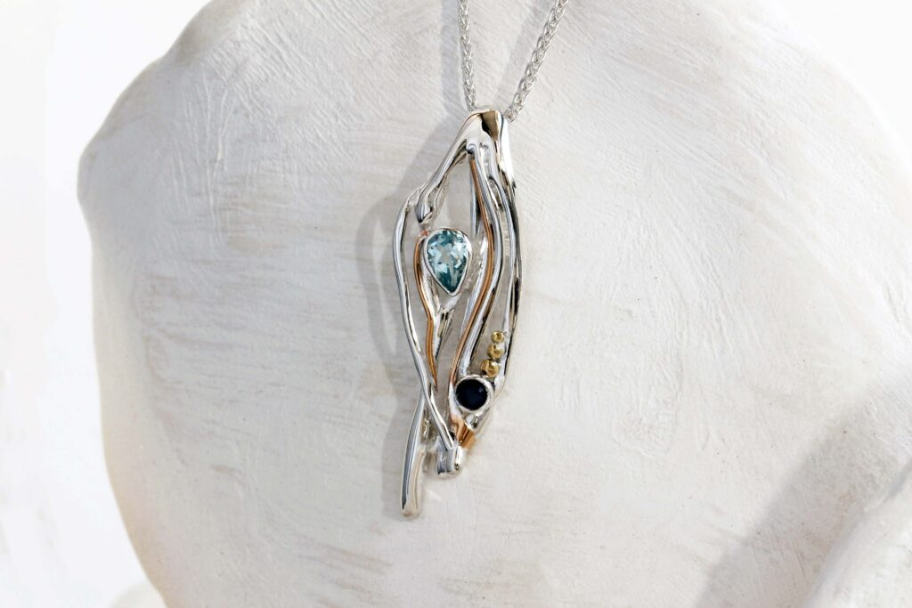 A Banyan Jewellery silver flowing pendant with blue topaz and freshwater black pearl